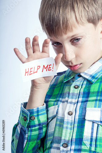 "Beautiful blond child shows a message ""Help me!"""