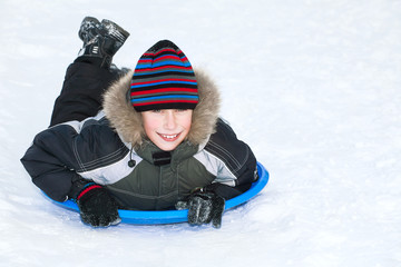 Cute child wearing winter jacket sledding on snow having fun