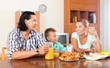 adult couple with teenager having breakfast with juice