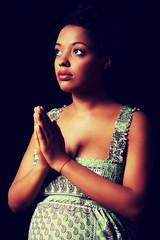 Young pregnant woman praying