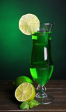 Glass of cocktail on table on dark green background