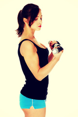 Teen girl holding dumbbells.