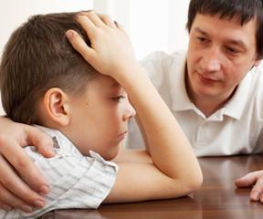 Father comforts a sad child