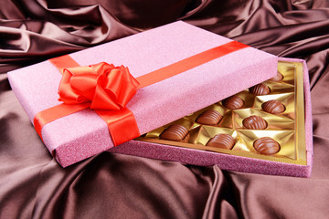 Delicious chocolates in box on brown background
