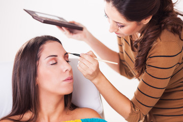 Female makeup artist darkening eyebrows.
