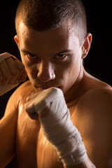 Portrait of a young Fighter on black background.