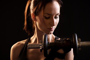 Portrait of a beautiful woman exercising with dumbbells.