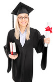 Woman in graduation gown holding diploma and books
