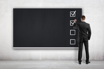 businessman drawing checklist on blackboard