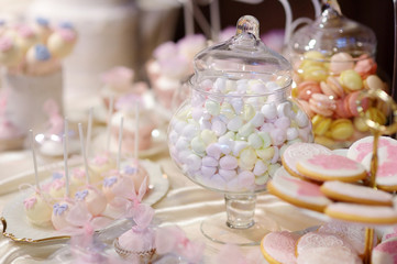 Decorated colorful candies on a pink table
