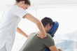 Physiotherapist giving back massage to man