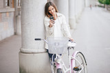 young woman texting on phone standing next to bike