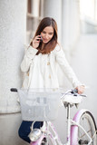 Young woman standing next to her bicycle and talking on the phon