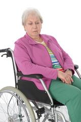 Seniorin im Rollstuhl schaut traurig