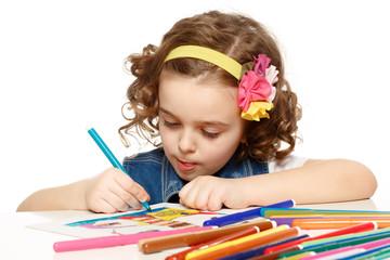 Little girl with felt-tip pen drawing in kindergarten