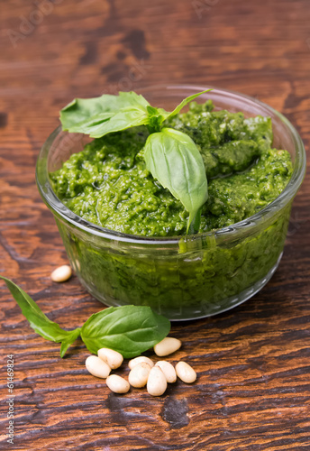 Fresh pesto in small glass bowl on wooden background