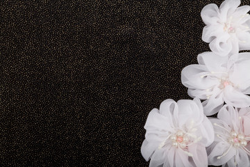 White flowers on black background with sequins