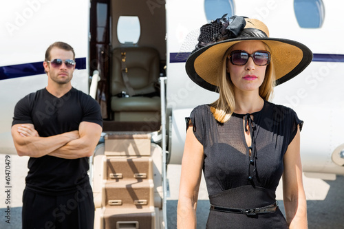 Beautiful Woman With Bodyguard Against Private Jet - 61470479