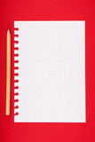 Torn blank lined notebook page with pencil on red background