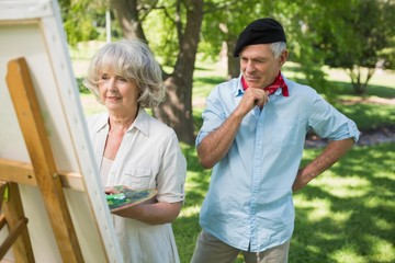 Man watching mature woman paint in park