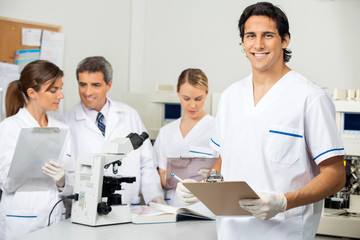 Male Scientist Holding Clipboard In Lab