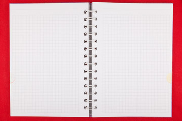 Notebook opened on blank pages on red background