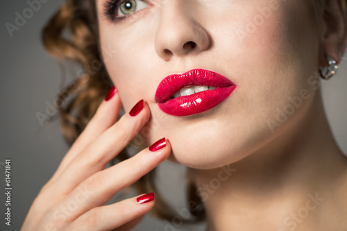 Close-up of red lips and polished red nails