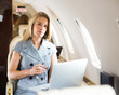 Confident Businesswoman Holding Wineglass In Private Jet