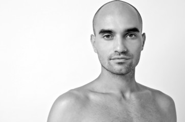 Bald Caucasian man with topless shoulders.Black and white photo.