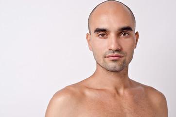 Bald Caucasian handsome man with topless shoulders.