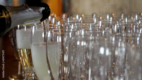 Waiter is pouring Champagne on Empty Glasses