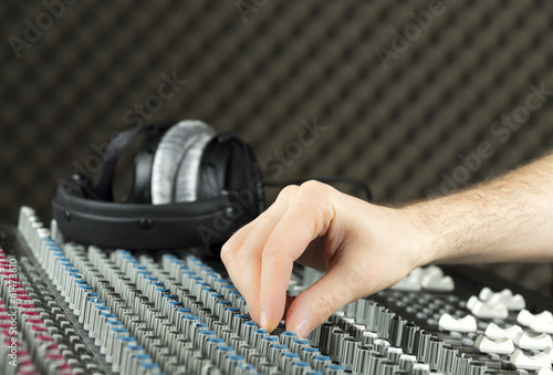 Closeup of a hand adjusting a studio mixer
