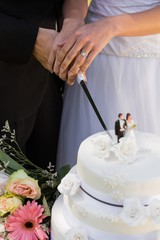 Mid section of newlywed cutting wedding cake