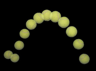 Bouncing tennis ball on black.