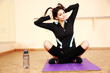 Young funny fit woman sitting on the yoga mat at gym