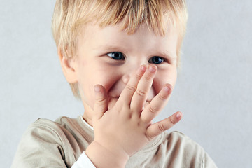 shy blond boy hide his nose and mouth with hid hand