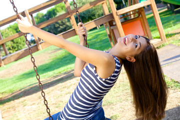 Happy woman with long hair swinging in park