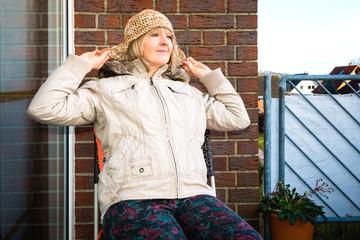 Frau erholt sich auf dem Balkon im Winter
