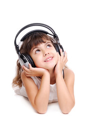 Little girl in headphones lying on the floor
