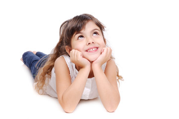 Little girl lying on the floor looking to the copy space area