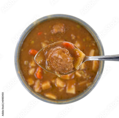 Spoonful of meatball stew with bowl underneath