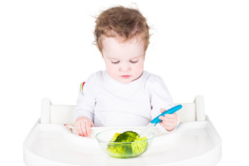 Little baby eating broccoli, isolated on white
