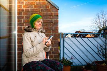 Frau draußen mit Smartphone im Winter