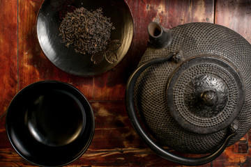 Japanese iron teapot and heap of tea leaves from top.