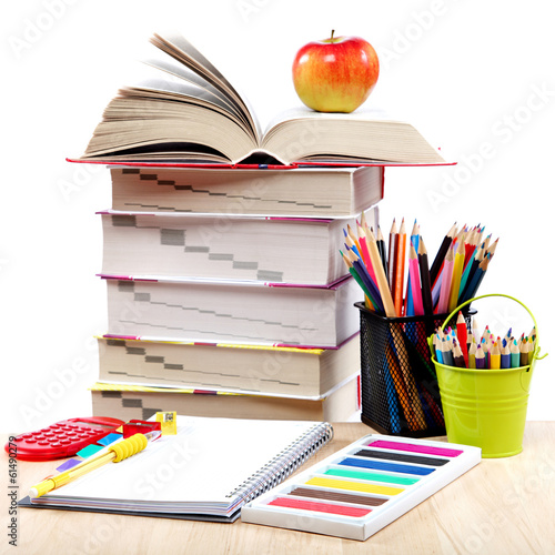 School and office supplies on a wooden table.