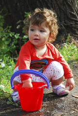 Summer near the river little girl playing with a bucket of water