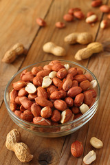 Raw peanuts or groundnuts on wooden table in glass bowl