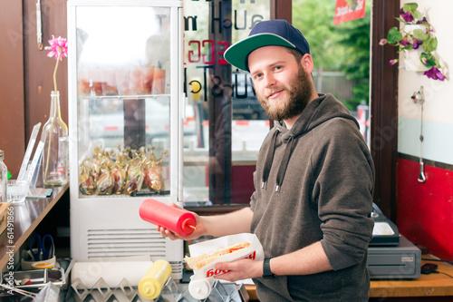 Fast Food Imbiss - Verkäufer mit Hotdog  - 61491866