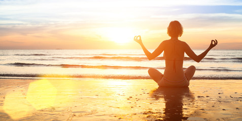 Silhouette of woman practicing yoga on the beach.