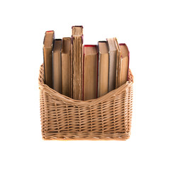Stack of old antique books in a wicker basket.